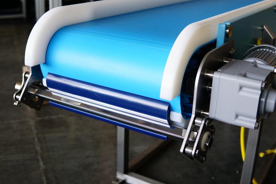 Scraper blade on sanitary conveyor removes bulk product, prevents